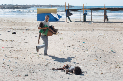 Civilians rushed to help after explosions hit a beach where children were playing in Gaza City. Four Palestinian boys died. Credit Tyler Hicks:The New York Times